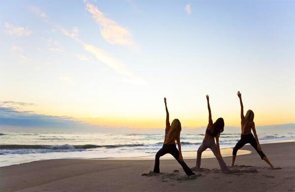 exercicios de yoga na praia em frente ao mar